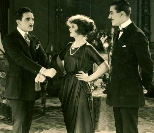 1920 vintage film scene of two gentlemen and a lady in pearls