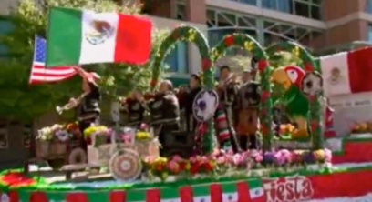 Just a-float with color in the Cinco de Mayo parade passing in front of baseball stadium (screenshot.khou.com)
