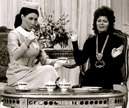 Two ladies having tea. 1971 Laugh-In pub.photo/ Lilly Tomlin as Mrs Earbore, the Tasteful Lady and Rita Hayworth/NBC/US PD:pub.date/no cr notice/Commons.wikimedia.org)