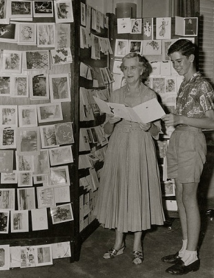 Mom and son in front of card display.1950's Christmas Cards in Australia. Oxley Linrary, Queensland /released to PD: exp cr/Commons.wikimedia.com