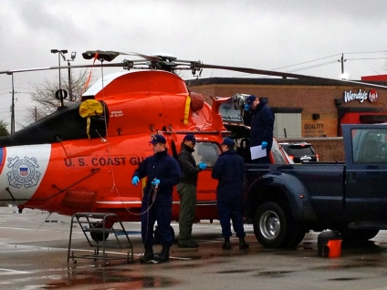 all rights reserved. Coast Guard examining engines for damage. No permissions granted. Copyrighted