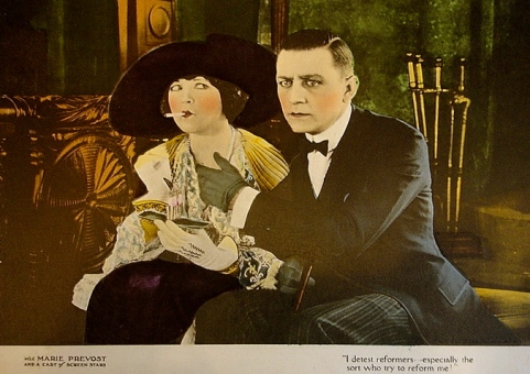"vintage film couple on couch.1922.""Beautiful and Damned"" film lobby card/Warner Bros./USPD.pub.date/Commons.wikimedia.org)"