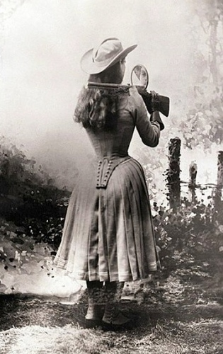 Annie Oakley shooting with mirror behind her back/Historyinpix/USPD.Pub.date/Commons.wikimedia.org)