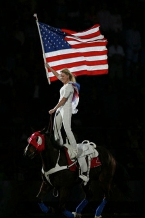 Girl standing on galloping horse with US flagFlag rider. www.rodeohouston.com