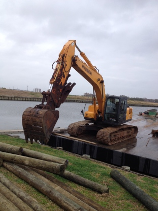 Backhoe (all rights reserved) on barge (no permissions granted) with pilings (copyrighted)