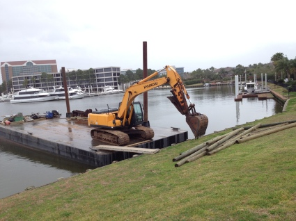 Barge (no permissions granted) with backhoe (All rights reserved) and pilings (Copyrighted)