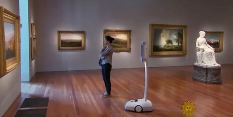 Robot and woman viewing painting with sculpture behind them (screenshot.CBS SUnday Morning Show/YouTube)