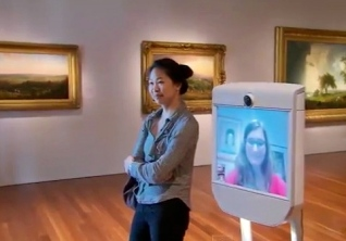 Woman with robot in gallery (screenshot CBS Sunday Morning/YouTube)