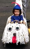 girl in shaggy dog art car (Milagros Graciano/ Art Car Parade FaceBook  screenshot)