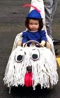 girl in shaggy dog art car (Milagros Graciano/ Art Car Parade FaceBook  screenshot)