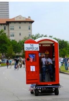 Red outhouse car. Crapper Art Car. 2015 Houston Art Car Parade/ Screenshot.khou.com)