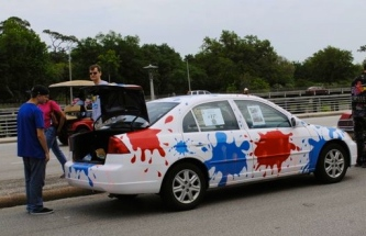 Art Car: white with paint ball splatters of red and blue. (2015 Houston Art Car Parade screenshot/khou.com)