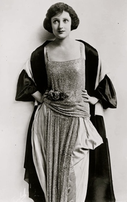 woman in vintage dress standing.Actress Carmel Myers/LOC.BAin Collection/Commons.wikimedia.org)