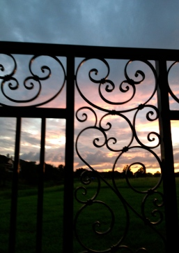 All rights reserved for this sunset seen through ornate iron fence. NO permissions granted. Copyrighted