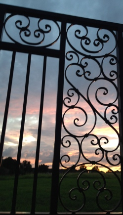 Sunset seen through ornate iron fence. ALL rights reserved Copyrighted.