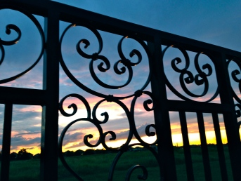 Sunset seen through elaborate ornate iron fence. ALL rights reserved. Copyrighted. NO permissions granted.