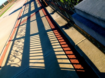 Shadows (ALL rights reserved) on sidewalk from wrought iron rail on bridge. NO permissions granted. Copy righted