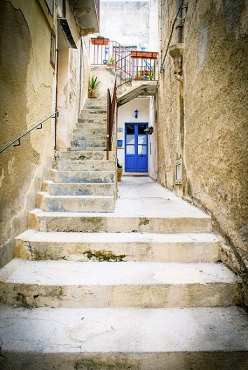 Blue door at end of long old stone alley with stairs (Strada di Favignana/Daniele Radavero/Flickr.DaRaZena/Commons.wikimedia.org)