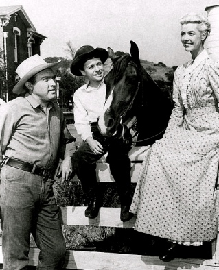 Vintage Western dressed Man, woman, and boy sitting on corral fence by horse. (1957. My Friend Flicka pub. picture. NBC:USPD.pub.date:Commons.wikimedia.org)