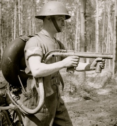 1944. Lifebuoy man-portabe flamethrower held by British soldier (PD released by UK government.War office photo by Woolridge:Imperial War Museum, H37975)
