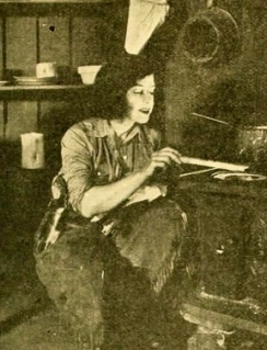"""woman cooking on wood burning stove /1919 film She Wolf""""/ Moving Picture World/Merit Film Corp./USPD. pub.date/Commons.wikimedia.org)"""