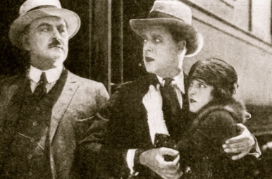 "Couple staring in fear at man (1921.""Luring Lips"" / Oct 1921 Jul-Dec Photoplay Mag/Universal Films/USPD.pub.date/Commons.wikimedia.org)"