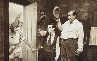 """Country woman and two men in farm house room.Lobby card for """"The Scarecrow"""" Buster Keaton. 1920. Schenck Production/USPD.Pub.date/Commons.wikimedia.org)"""