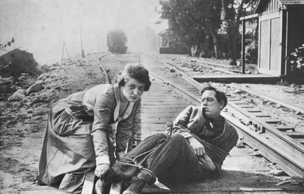 """Woman freeing man tied to train tracks. 1916. """"A Lass of the Lumberlands"""". Mutual film lobby card/USPD.pub.date/Commons.wikimedia.org)"""