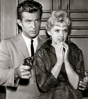 1960 Robert Conrad with a gun and frightened Connie Stevens staring at the distance. TV show ofHawaiian Eye. 1960. Warner Bro.(USPD.pub.date, no cr/Commons.wikimedia.org)