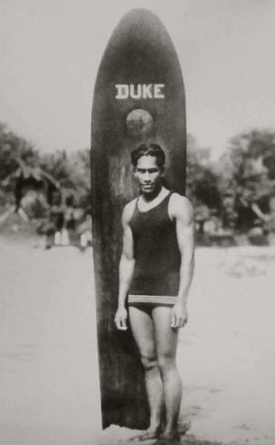 surfer.Duke Paoa Kahanamoku with Waikiki board. 1910-15/ Malama Pono Ltd./USPD. pub.date, reprod of PD art/Commons.wikimedia.org)