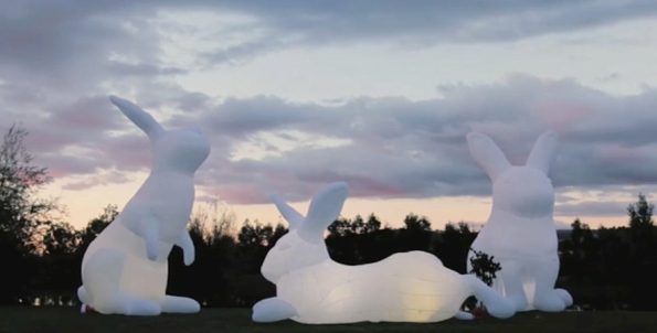 3 giant inflatable bunnies posed by the lake at dawn by the lake at dawn. Intrude Art Installation/Vimeo