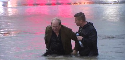 ABC 13. Reporter assisting stunned man who drove into flooded street. (abc13.com)