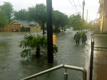 men wading down flooded street.chron.com