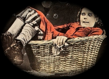 "weird looking girl sitting in a basket.(1920. lobby card for ""Suds"". Pickford:/ United Artists/ USPD: pub.date/Commons.wikimedia.org)"