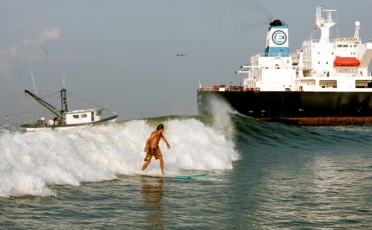Man surfing among shrimp boat and tanker. (tankersurfcharters.com/photo)
