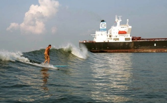 Man surfing on wave created by tanker. (image tanksurfcharters.com)