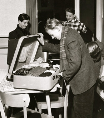 Man looking in suitcase. (mily.suitcase inspection.1957.Bundes archiv, B145 Bild-FOO4909-001/Uterberg, Rolf/Commons.wikimedia.org)