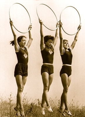 Girls in vintage gym clothes holding up hoops. 1957. (German Federal Archives.Bundesarchiv,Bild 183-48070-0004/Commons.wikimedia.org)