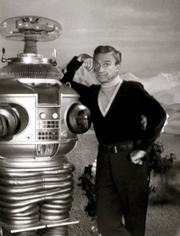 "man stanading next to robot. robot. ""Lost in Space"" publicity photo with J.Harris1967/CBS (USPD:no cr.markings, pub.date/Commons.wikimedia.org)"