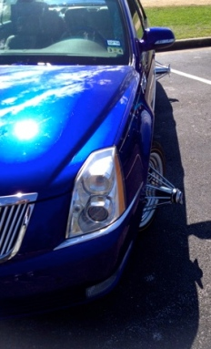 Blue show car. SLAB with pokes: gladiator-style wheel accessory. (image: the truthaboutcars/ primer on Houston Slab culture)