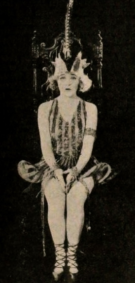Seated woman in 1920 costume. Mae Murray. From Exhibitors Heralds (jan-mar. 1920) / Famous Players. Lasky Artcraft/ Paramount (USPD.pub.date/Commons.wikimedia.org)