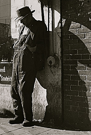 Man in overalls leaning against by old storefront. 1935 Dorothea Lange1(1895-1965)FDR Pres.Lib./ USPD: pub.date, by Fed employee (Commons.wikimedia.org)