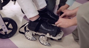 Stroke patient in wheel chair strapping GEMS shoe on. SciTech Now episode 313 YouTube:Wpsu.jpeg