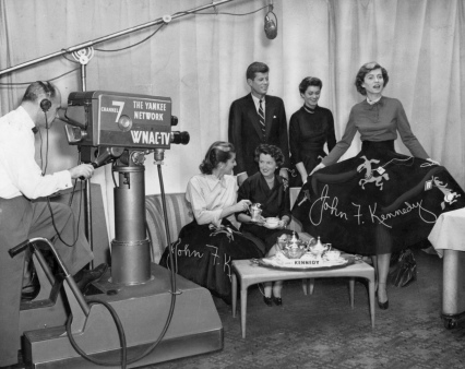 1952 Kennedy Tea with elegant silver service and full skirts featuring Kennedy slogan (JFK, his mother and sisters)TV cameras filming one of 33 campaign teas to support run for US Senate. (USPD: pub.date/Commons.wikimedia.org)