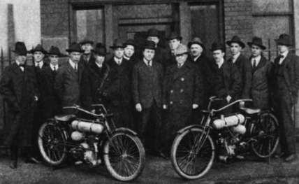 Men in vintage suits behind vintage motorcycles.1917. Sales and administrative force of Cleveland Motorcycle Mgg. Co. Image from Motor Cycle Illustrated (USPD: pub.date/Commons.wikimedia.org)