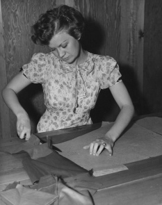 Woman learning to sew with cardboard pattern..1936. NARA (PD. pub.date, by fed employee/Commons.wikimedia.org)