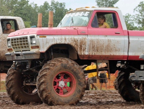 Very muddy jacked up pickup truck with huge tires. (Travelchannel.com)