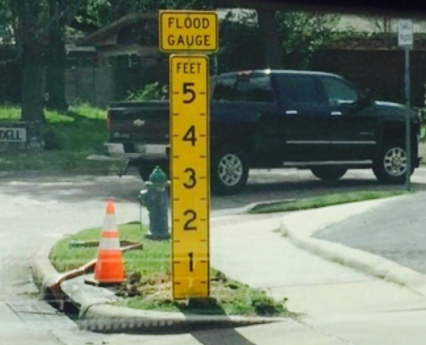 Yellow sign in street median showing possible water height in floods (Click2houston)