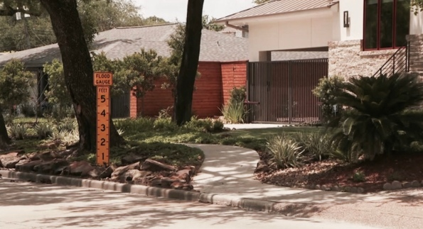 Large flood gauge sign in front of house. (click2houston)