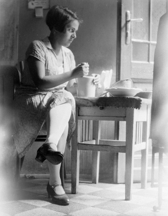 Woman at kitchen table. 1930's (USPD. Pub.date/Commons.wikimedia.org)